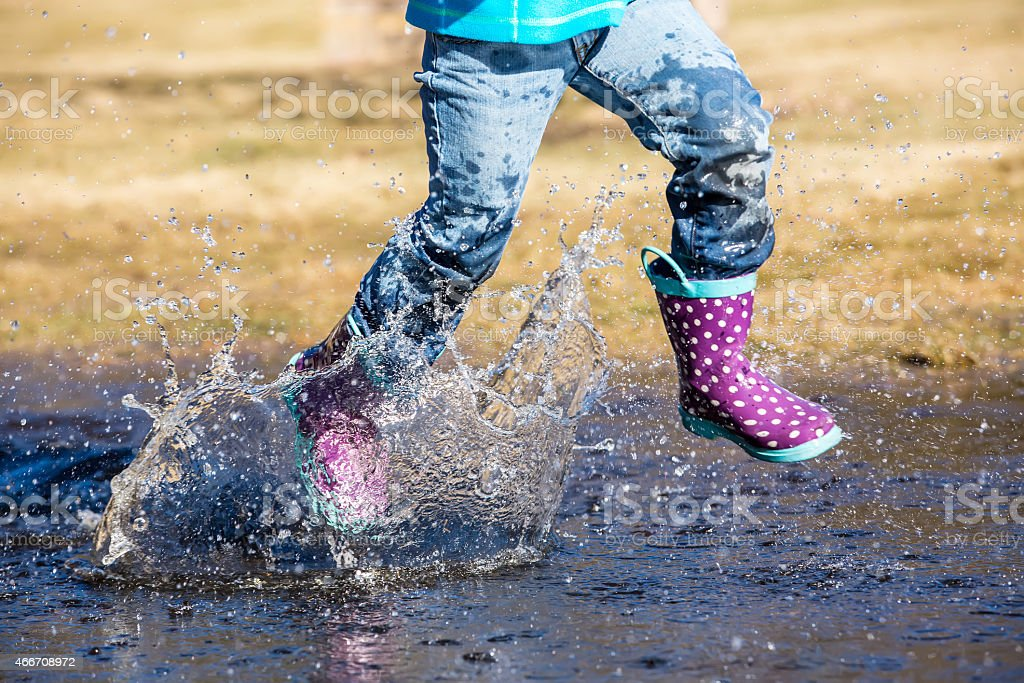 Girl Running Through Large Water Puddle in Early Spring stock photo