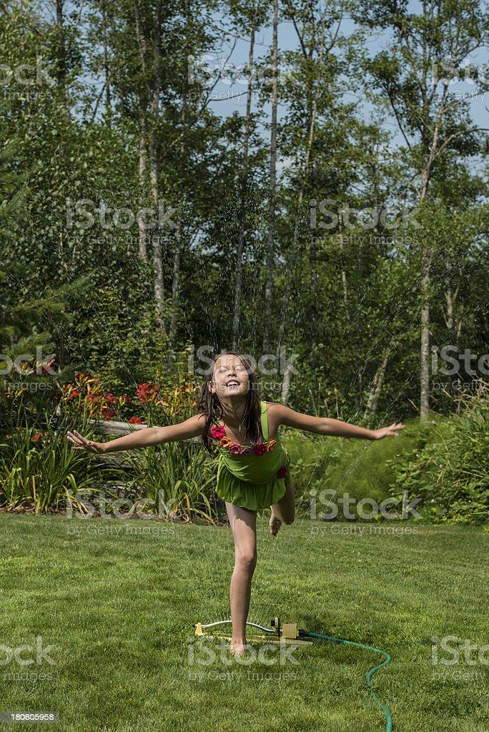 Girl Running Through Sprinkler On Hot Summer's Day stock photo
