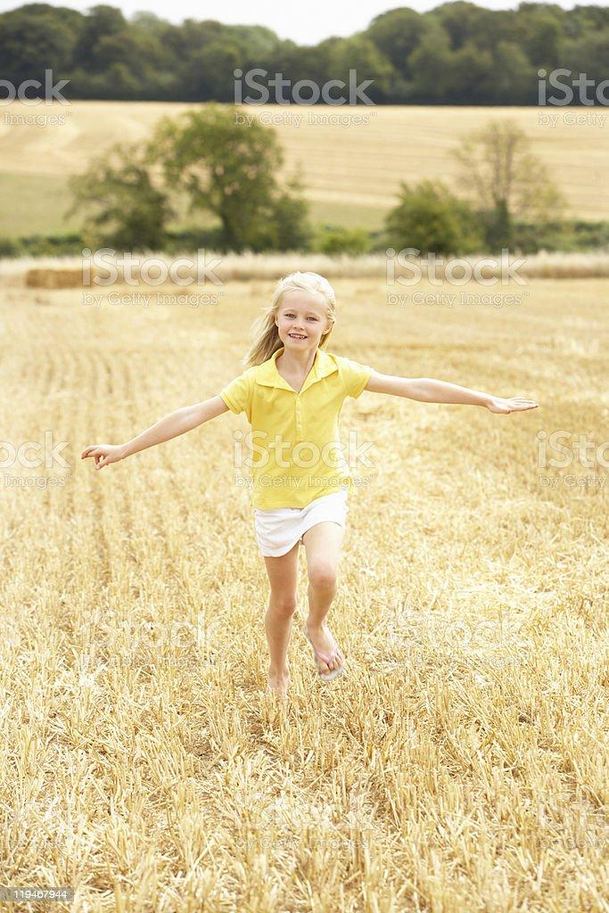 Girl Running Through Summer Harvested Field stock photo