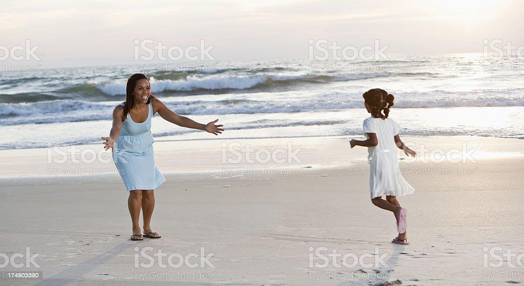 Girl running to mother on beach stock photo