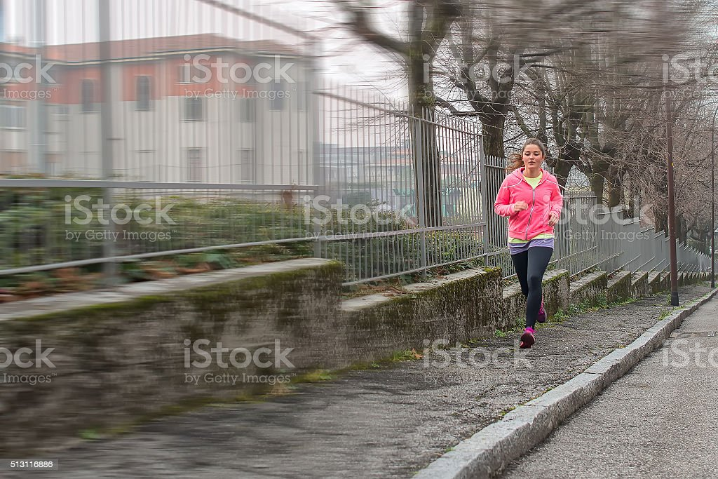 Girl runs on the sidewalk in the city stock photo