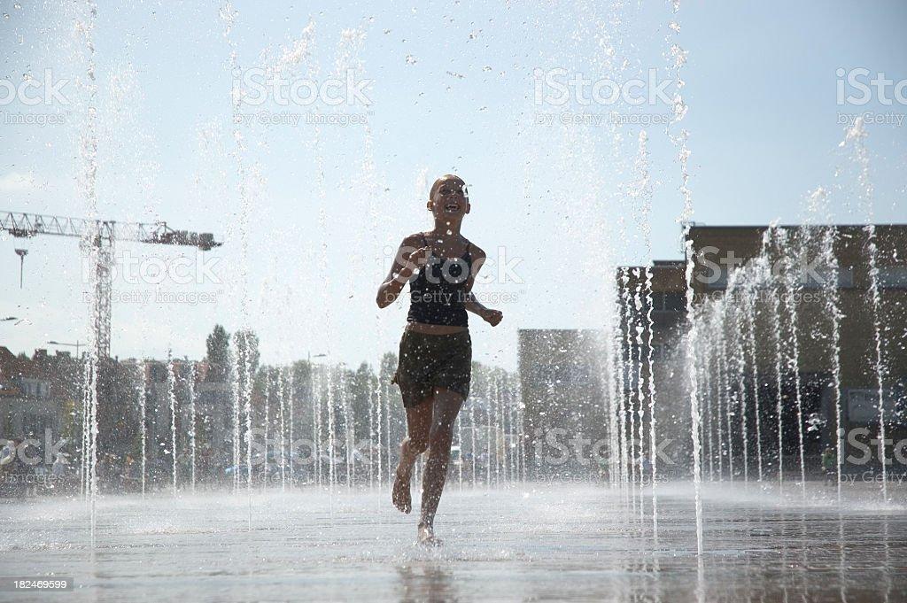 Girl runs through fountain royalty-free stock photo