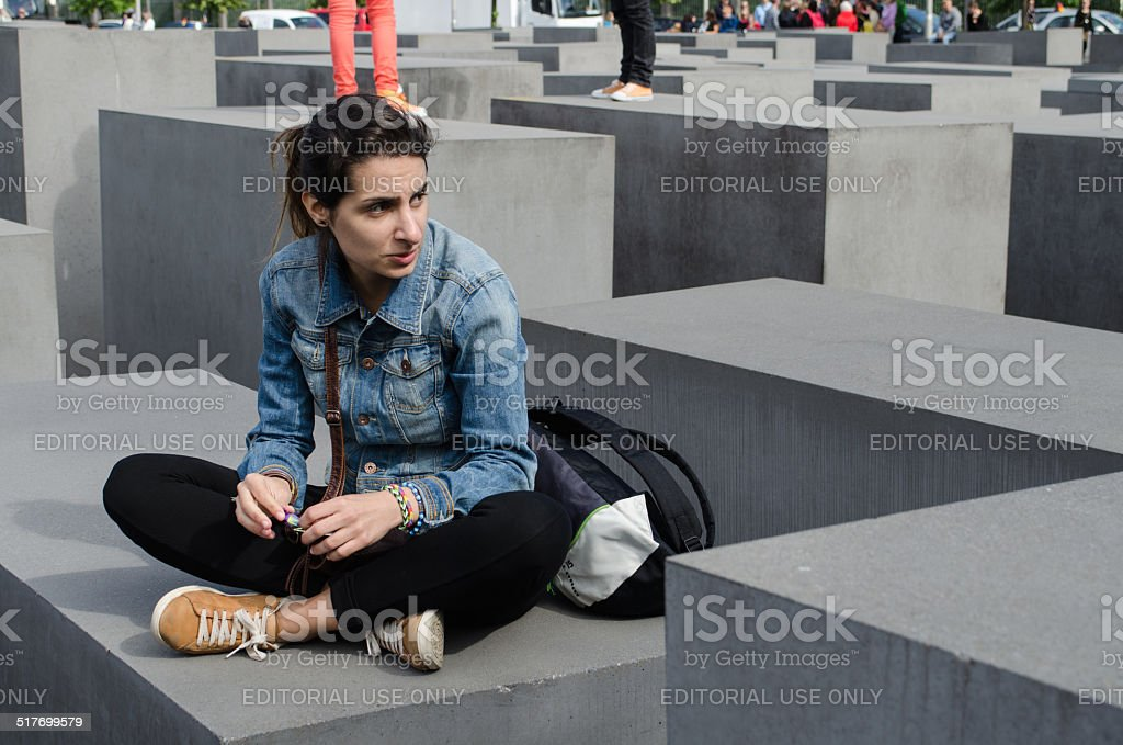 Girl sat on the Holocaust Memorial in Berlin stock photo