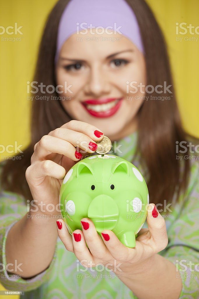 Girl saving money in a piggy bank stock photo