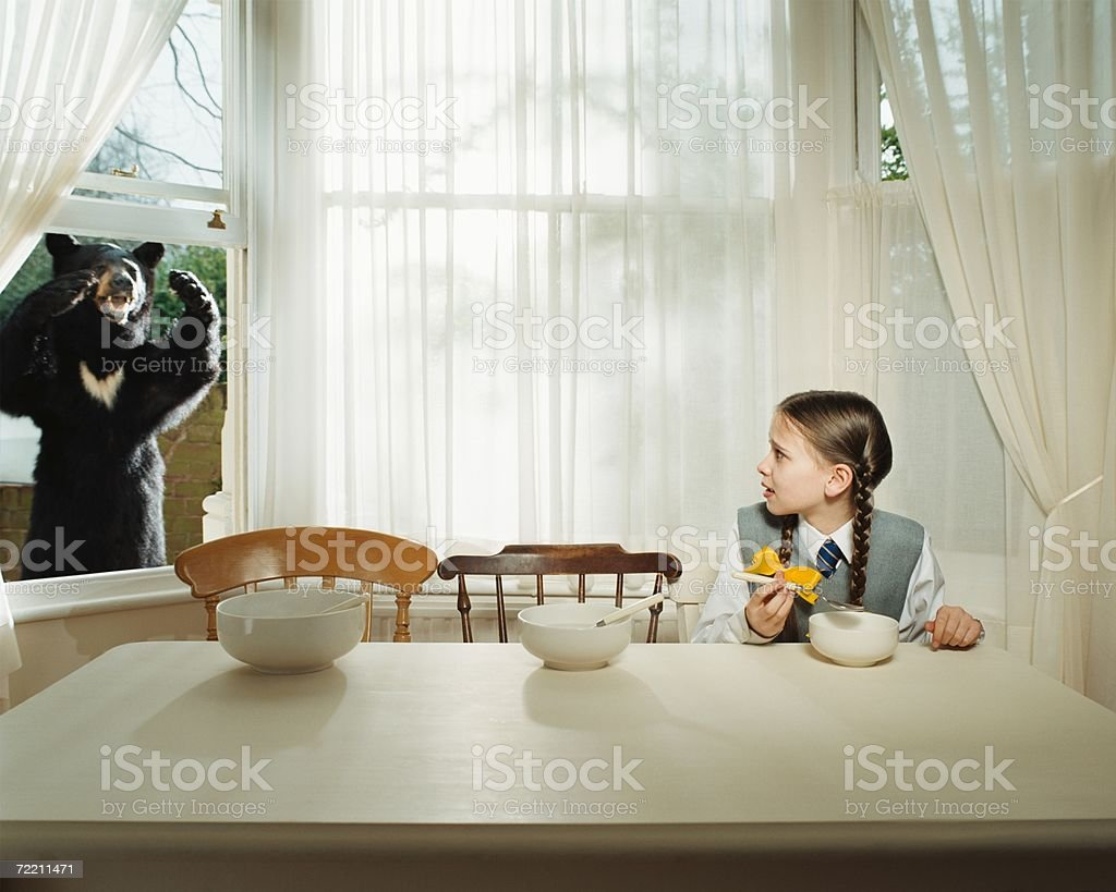 Girl scared by bear at the window stock photo