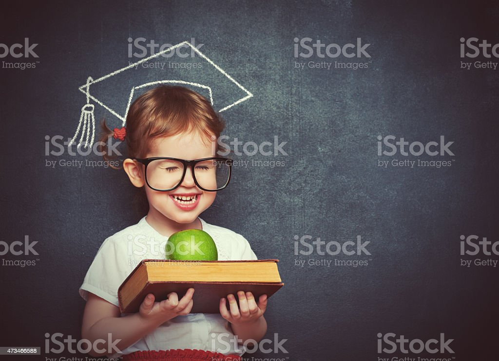 girl schoolgirl with books and apple in a school board stock photo