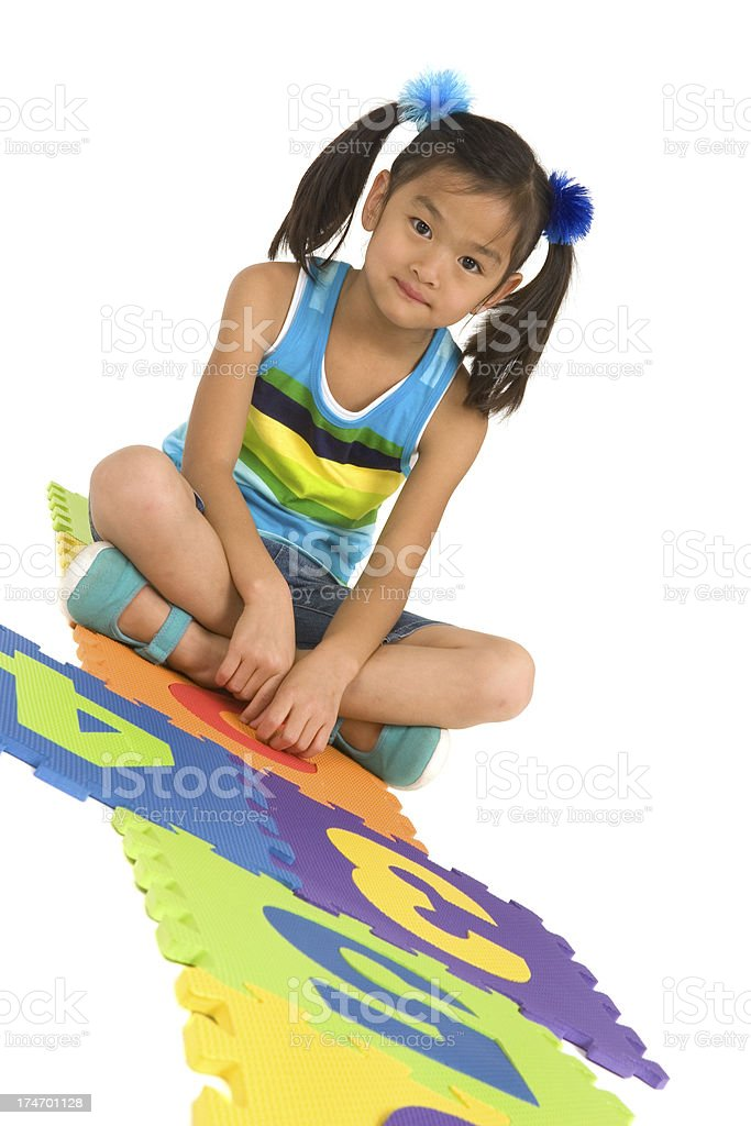 Girl seated on hopscotch tiles royalty-free stock photo