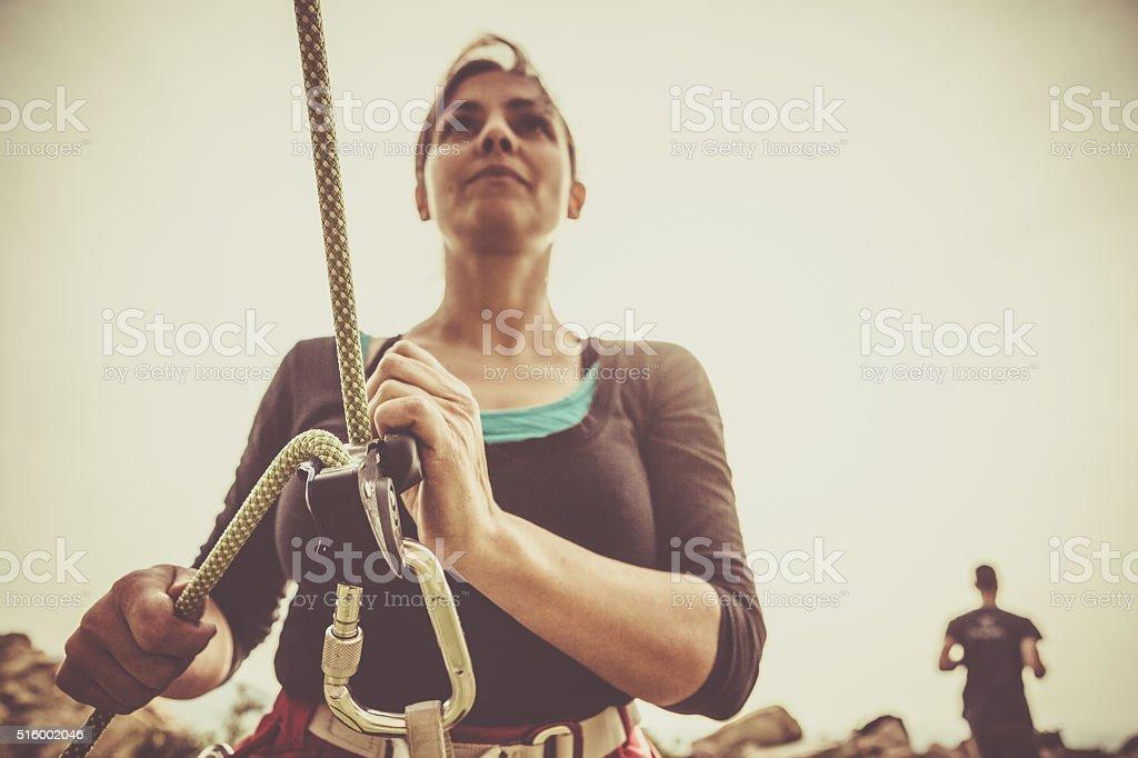 Girl securing rock climber while freeclimbing stock photo
