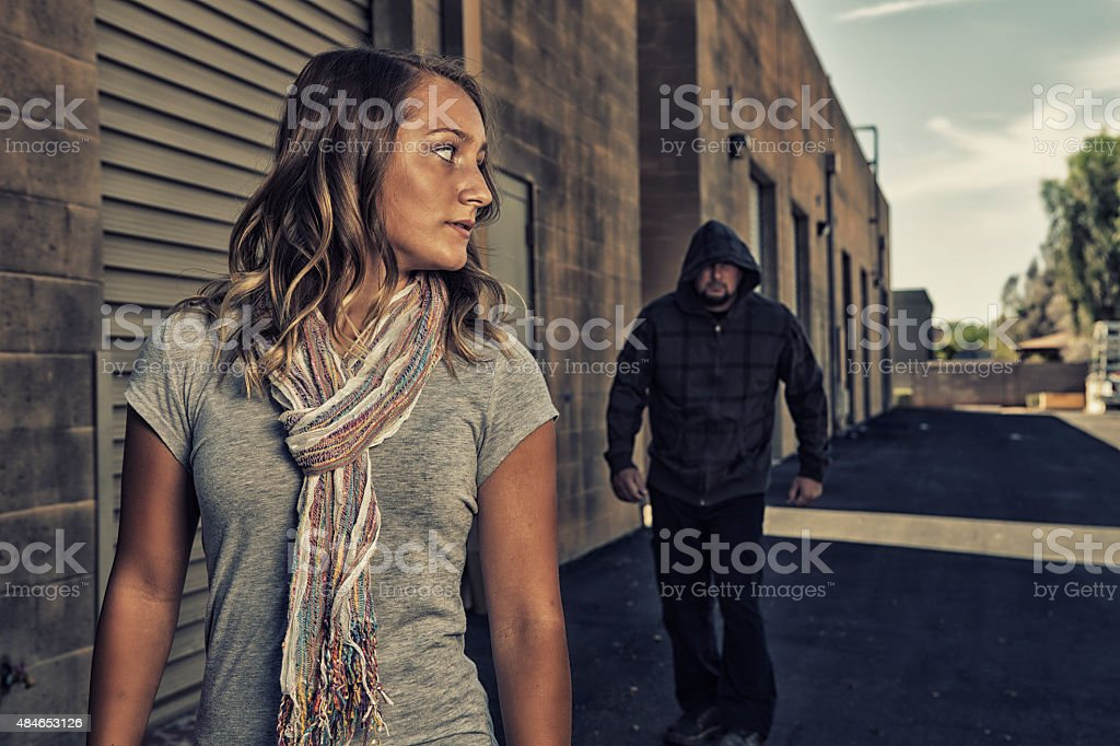 Girl sees a scary man walking behind her. stock photo