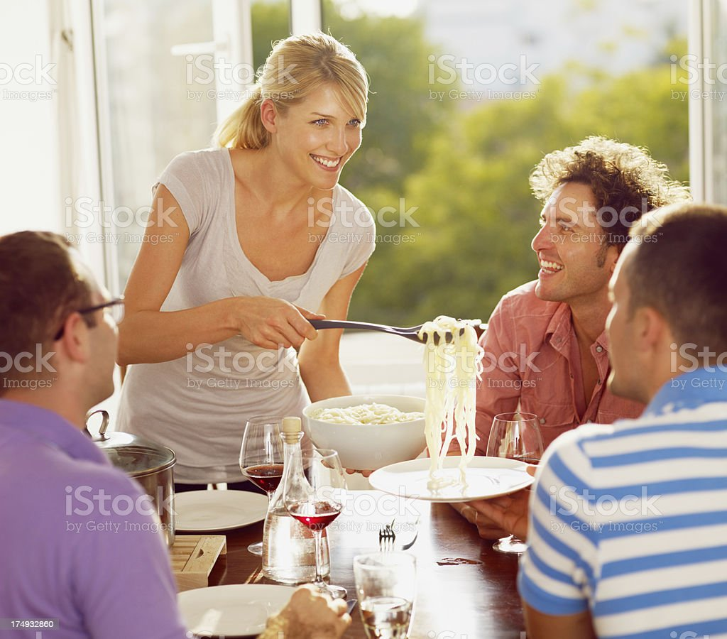 Girl serving pasta to her friends royalty-free stock photo
