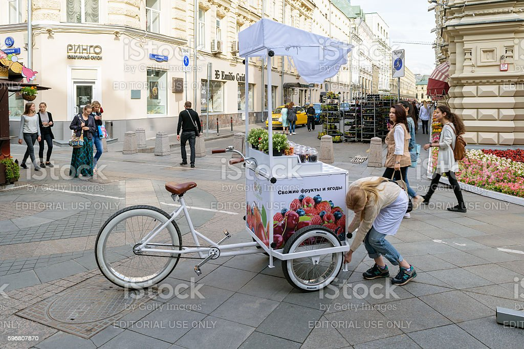 Girl sets the counter with a refrigerator, attached to bike stock photo