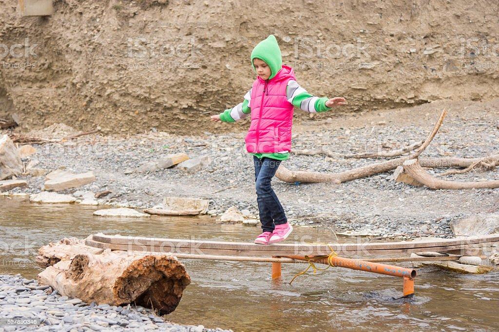 Girl seven years is on rickety bridge over stock photo