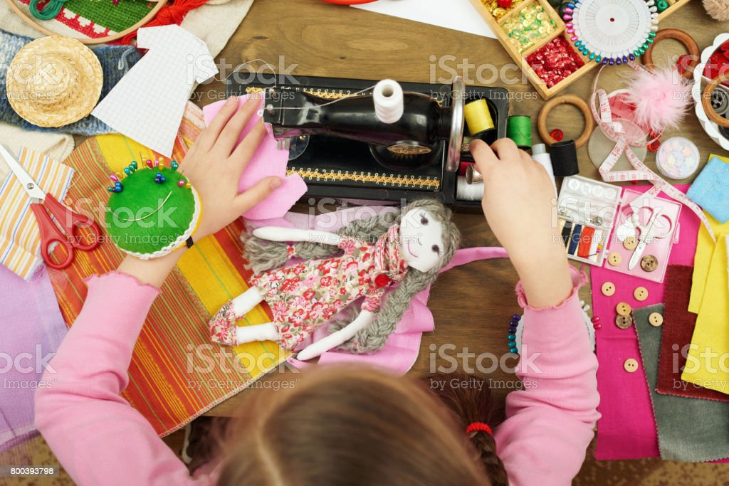 girl sews doll clothes, top view, sewing accessories top view, seamstress workplace, many object for needlework, handmade and handicraft stock photo