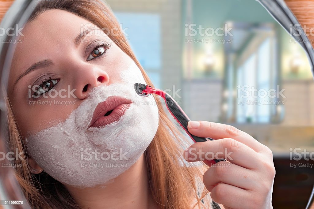 girl shaves in mirror stock photo