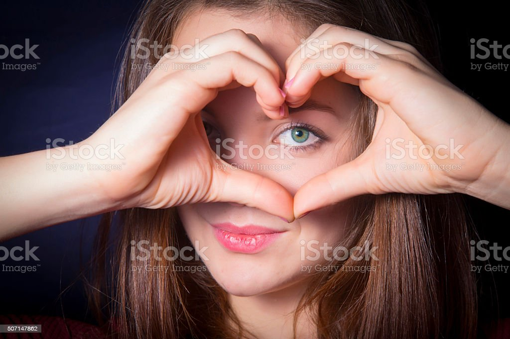 Girl show heart shape hands over her eye royalty-free stock photo