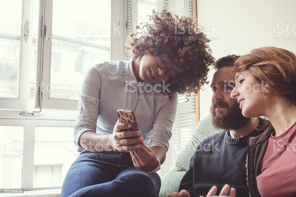 Girl showing a picture on her mobile phone to friends stock photo