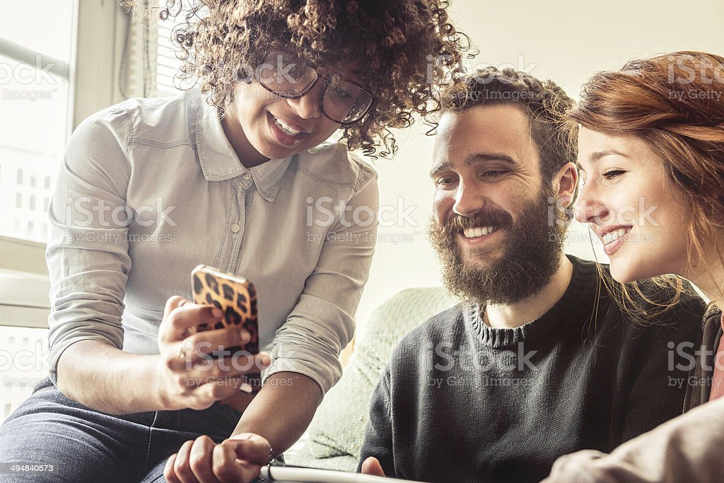 Girl showing a picture on her smartphone to friends stock photo