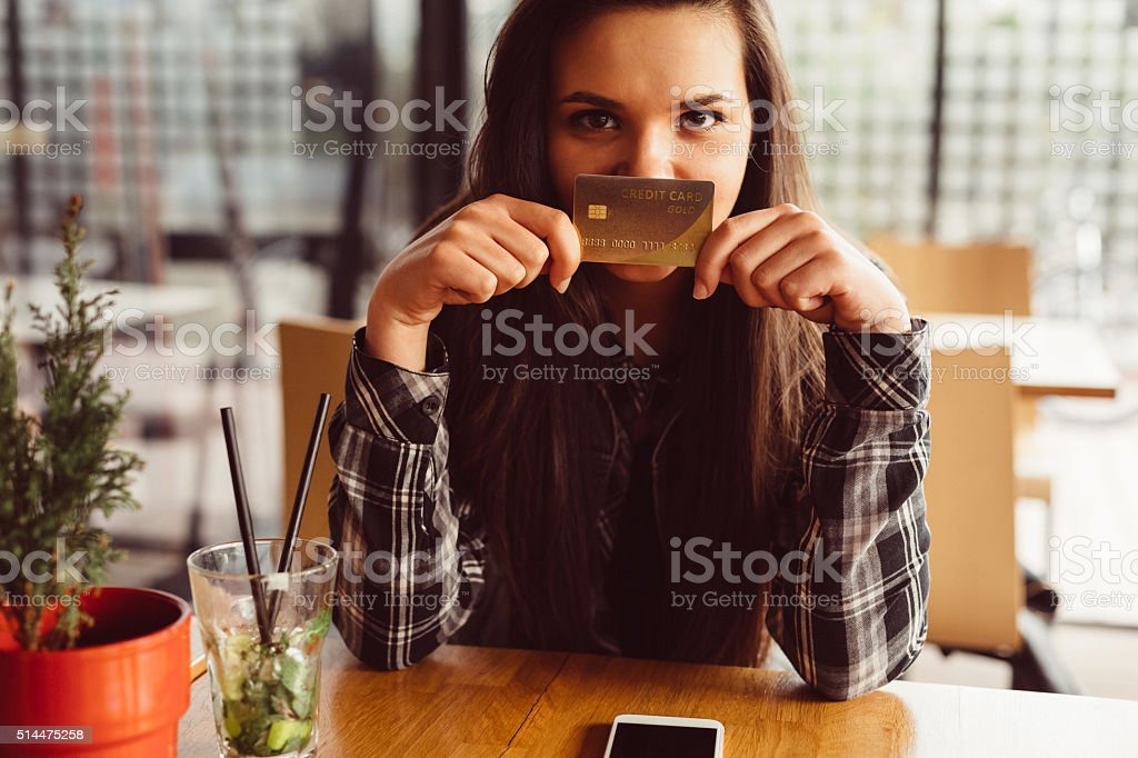 Girl showing credit card to the camera stock photo
