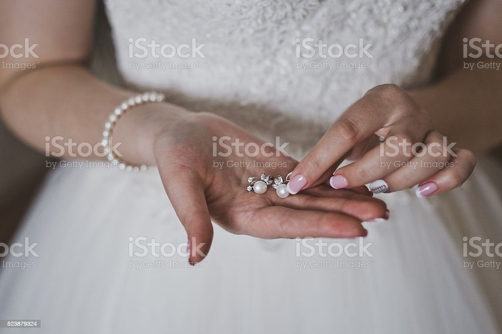 Girl showing earrings with pearls stock photo