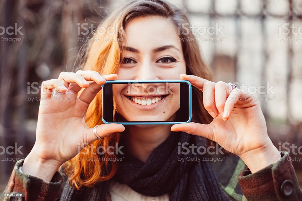 Girl showing fun selfie with toothy smile stock photo