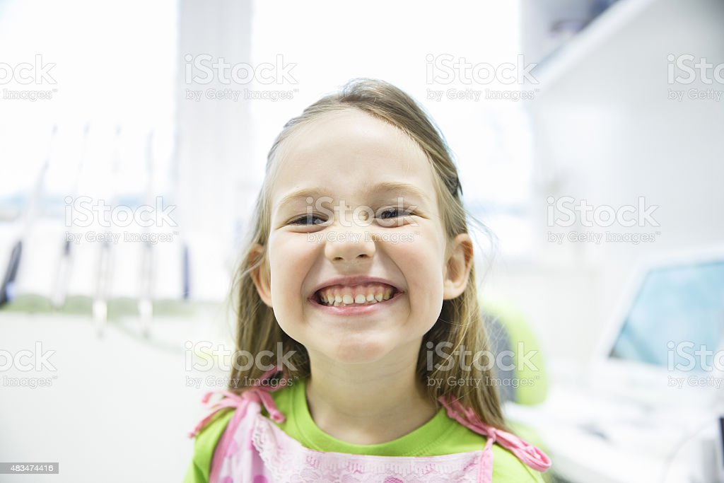 Girl showing her healthy milk teeth at dental office stock photo