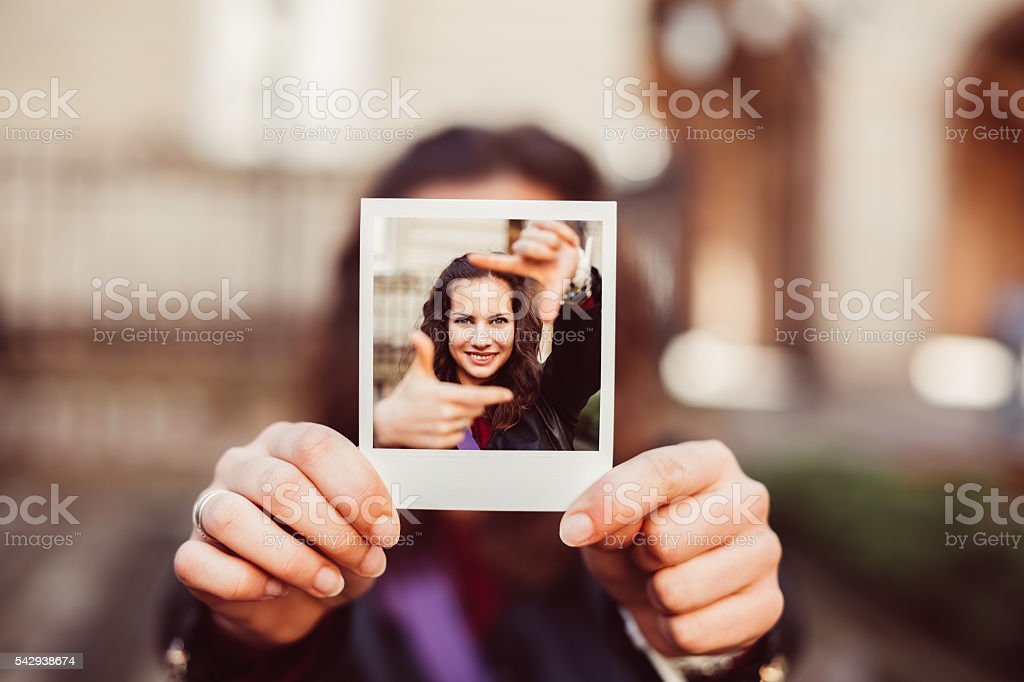 Girl showing instant photo of hand framing concept stock photo