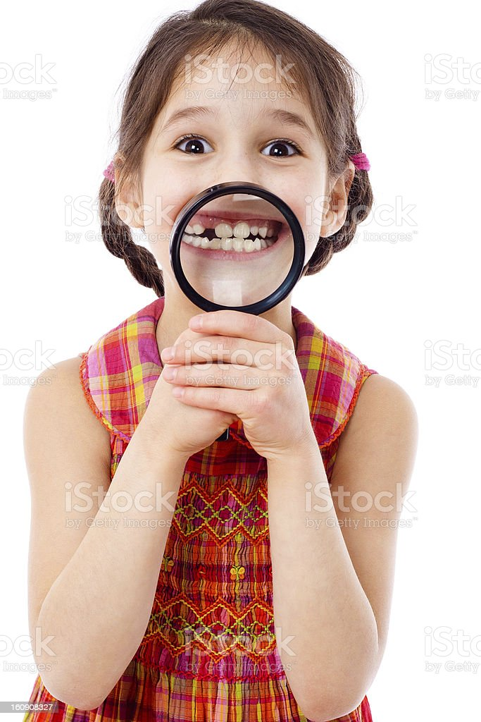 Girl showing teeth through a magnifier stock photo