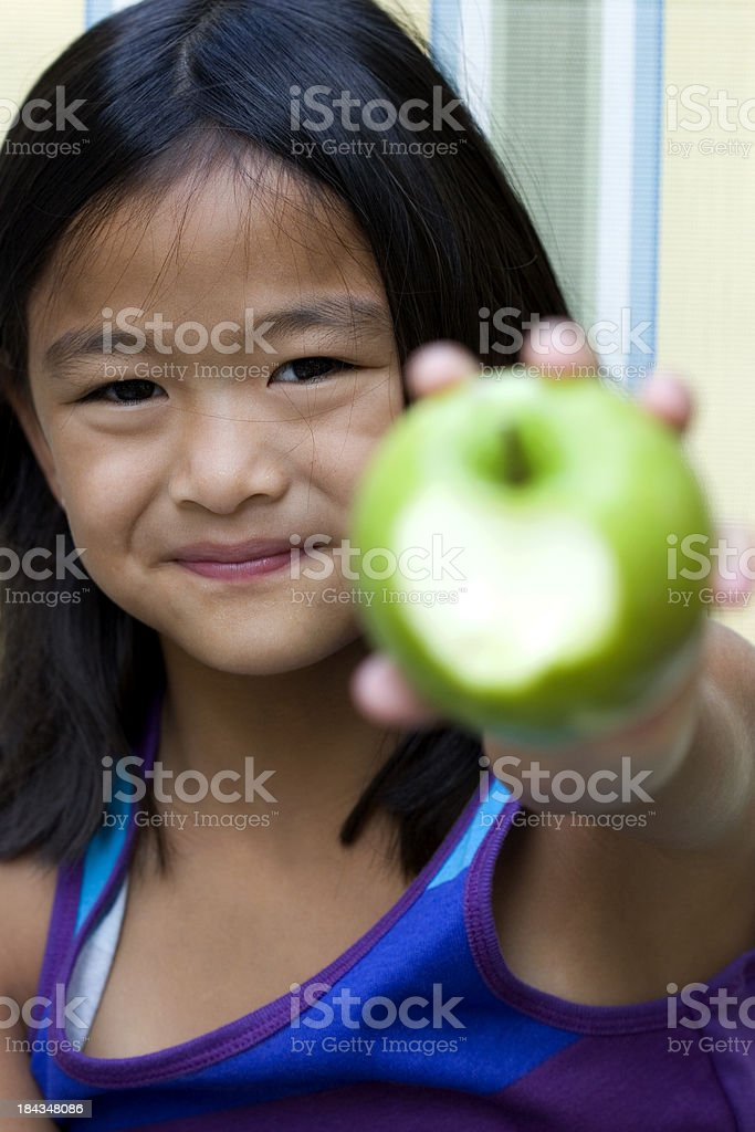 Girl shows apple with missing bite royalty-free stock photo