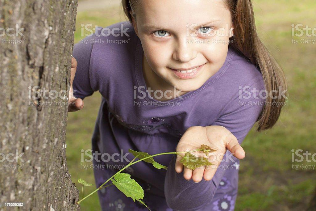 Girl shows green shoot of tree royalty-free stock photo