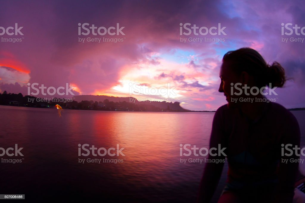 Girl silhouette under a fire red sunset stock photo