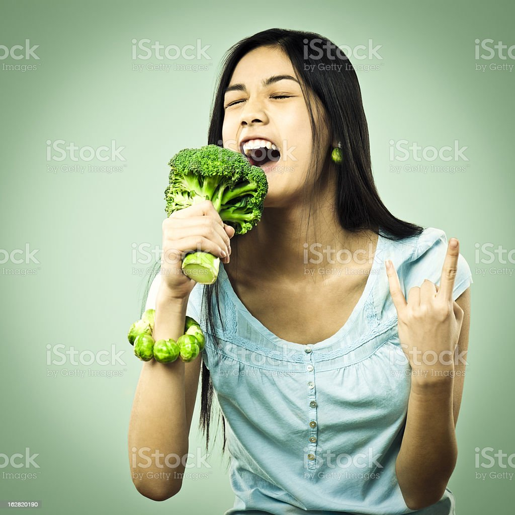 Girl singing in a broccoli microphone stock photo