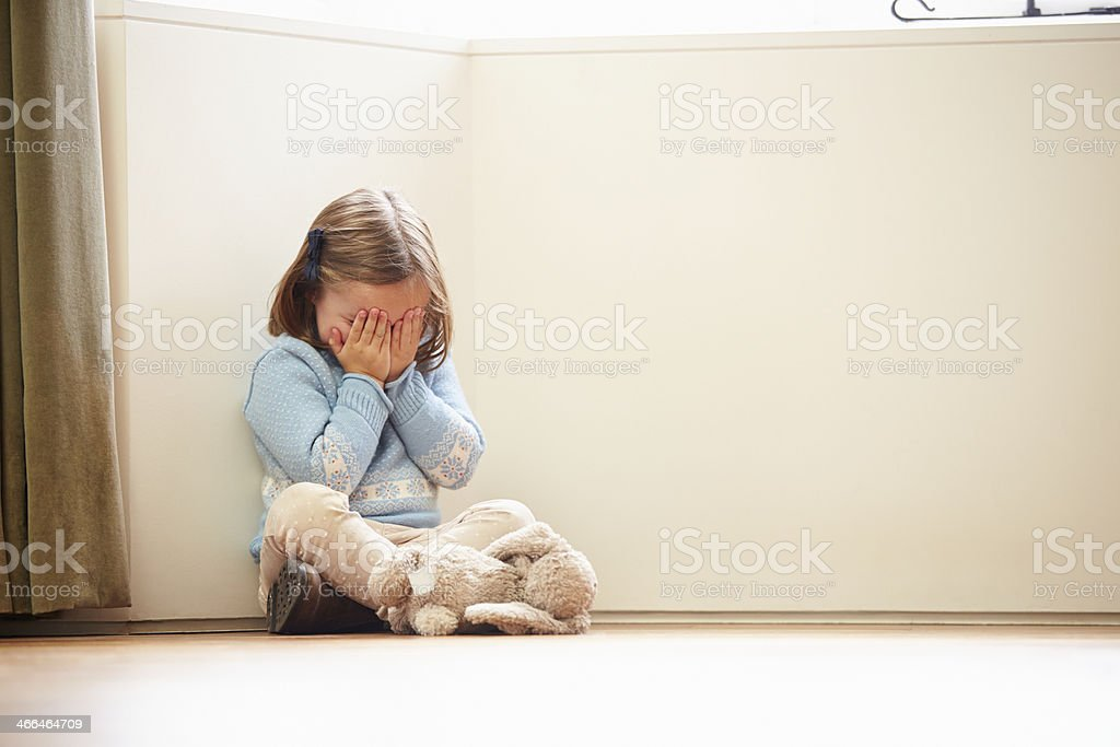 A girl sits at a corner, covering her face with her hands stock photo