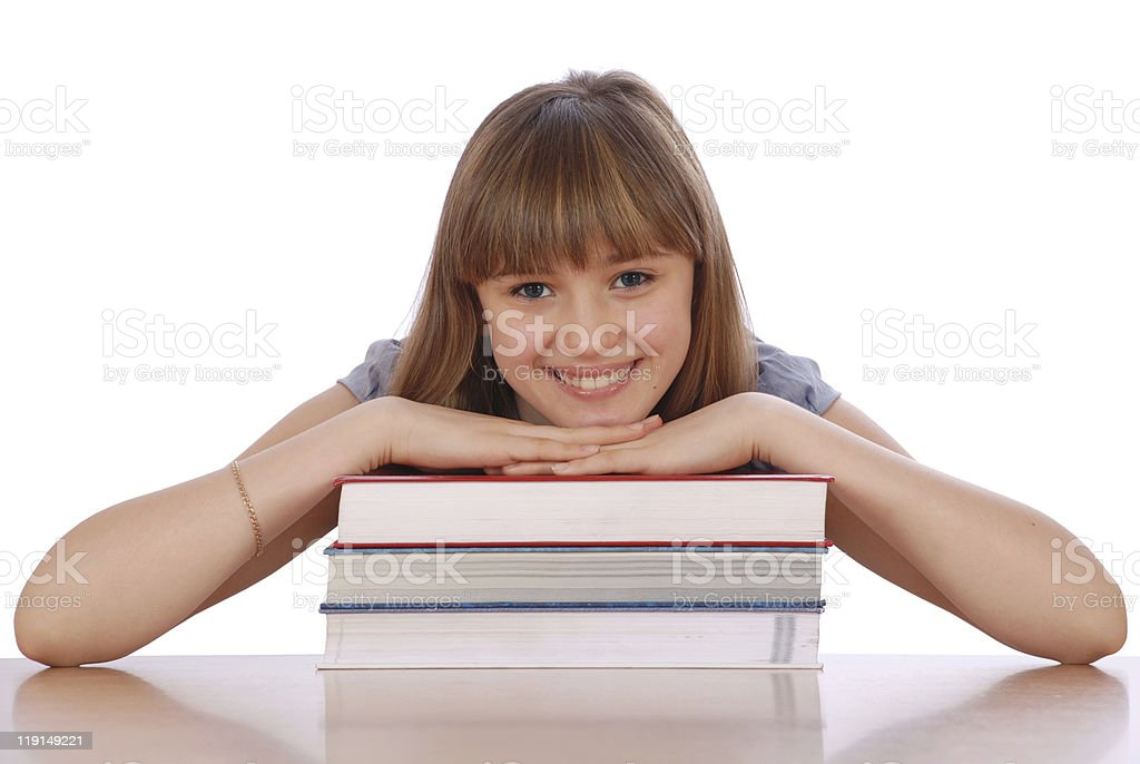 Girl sits at table and has put hands stock photo