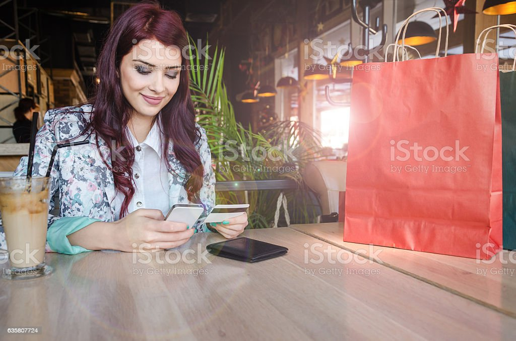 Girl sits at the table and buys over the Internet stock photo