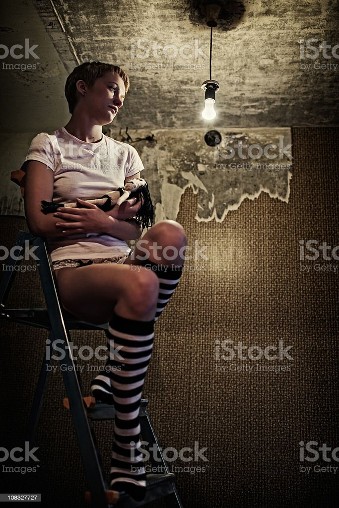 Girl sits high on a ladder with gothic doll. royalty-free stock photo