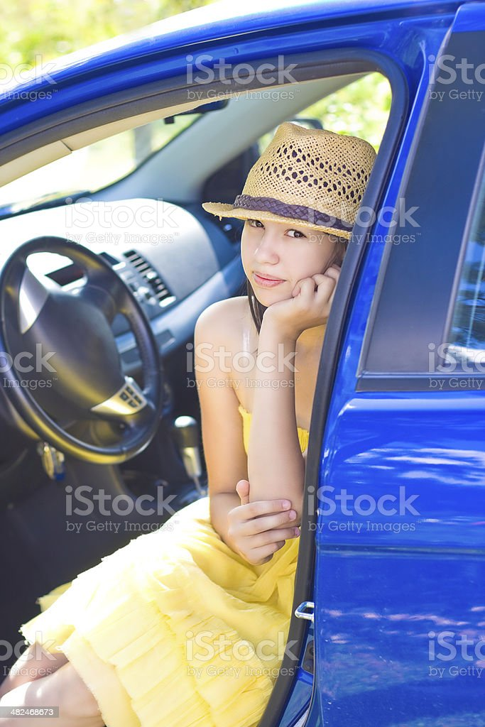 Girl sits in blue car royalty-free stock photo