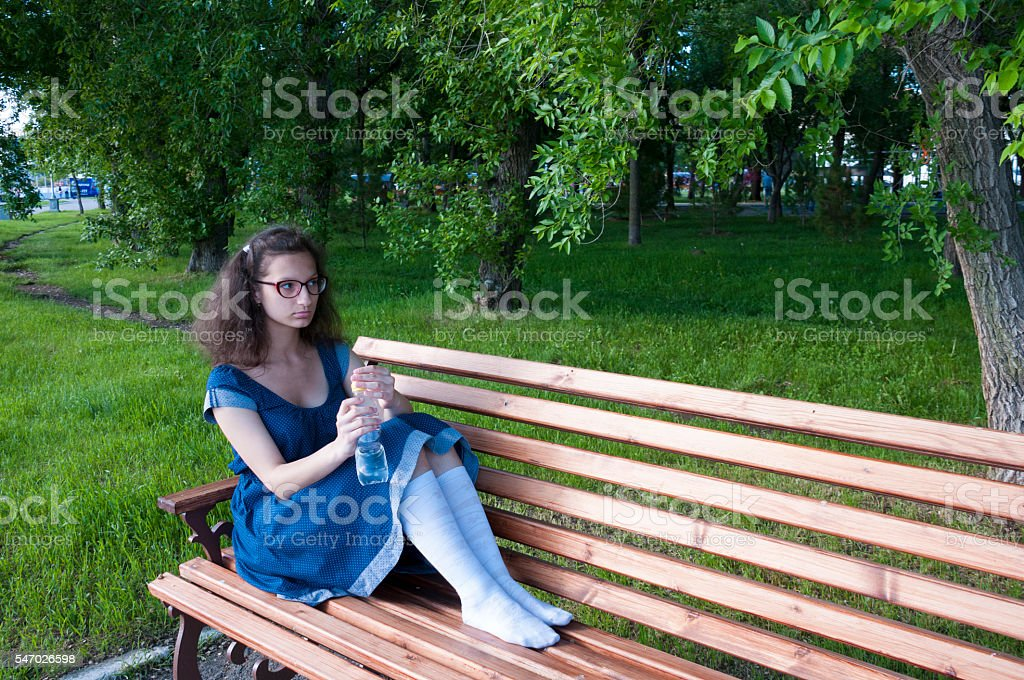 Girl sits on a bench with a bottle of water stock photo