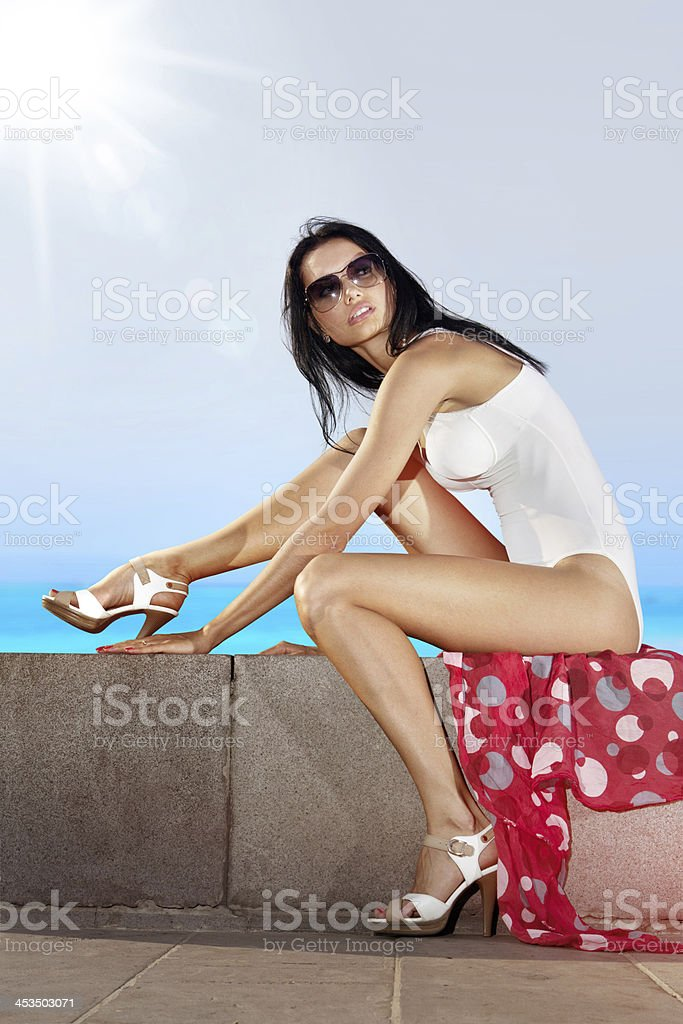 girl sits on quay stock photo