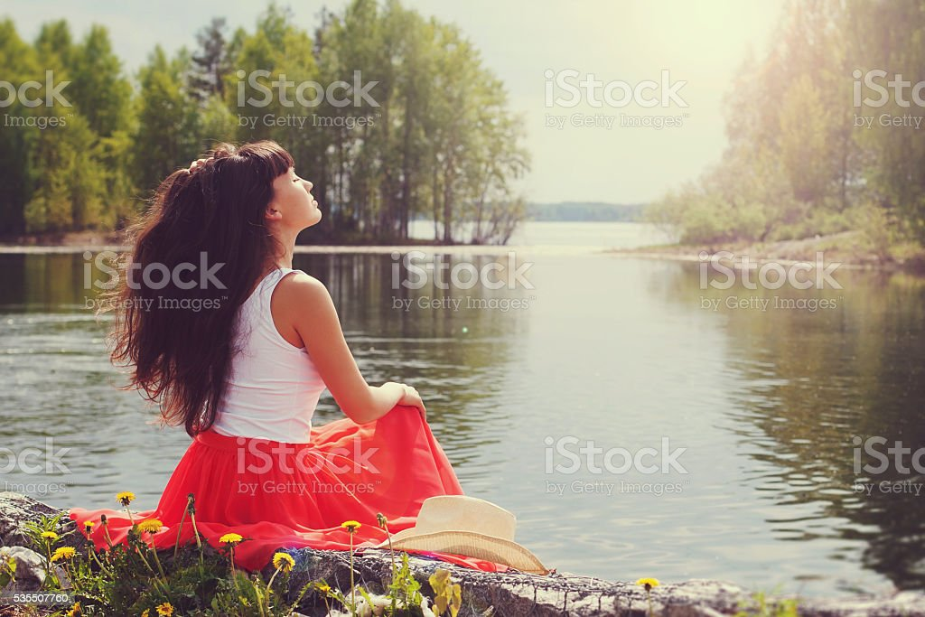 Girl sits on the bank of lake. stock photo