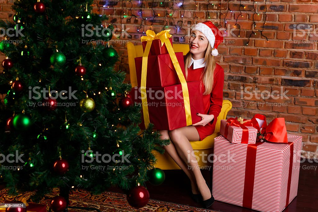 Girl sits with great gift near the Christmas tree stock photo
