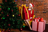 Girl sits with great gift near the Christmas tree