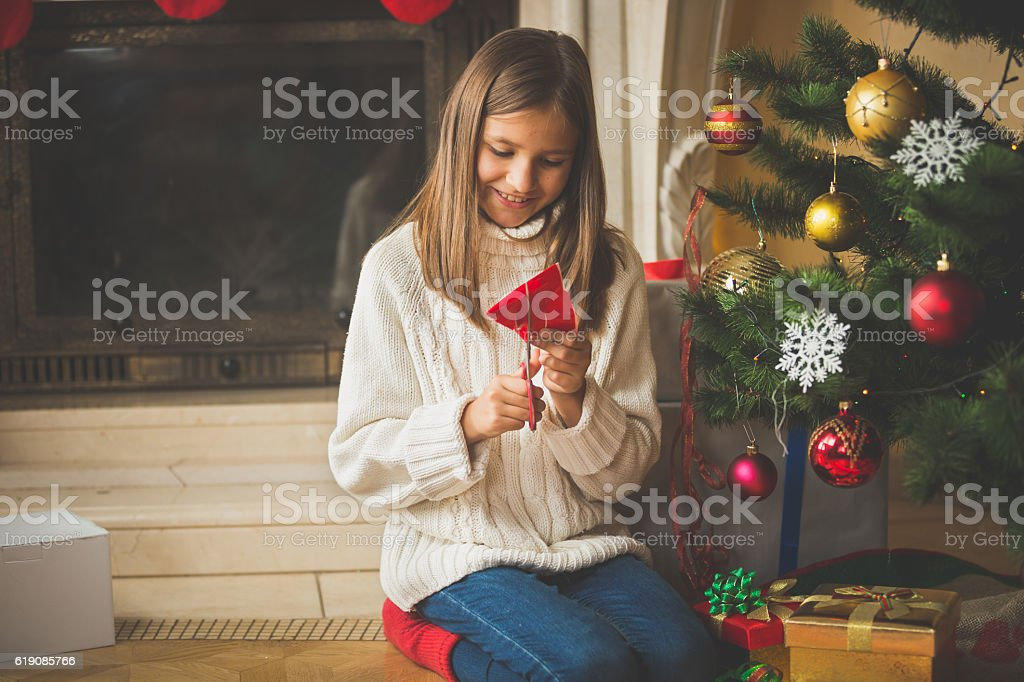 Girl sitting at Christmas tree and cutting decorations of paper stock photo