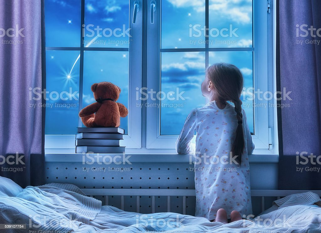 girl sitting at the window stock photo