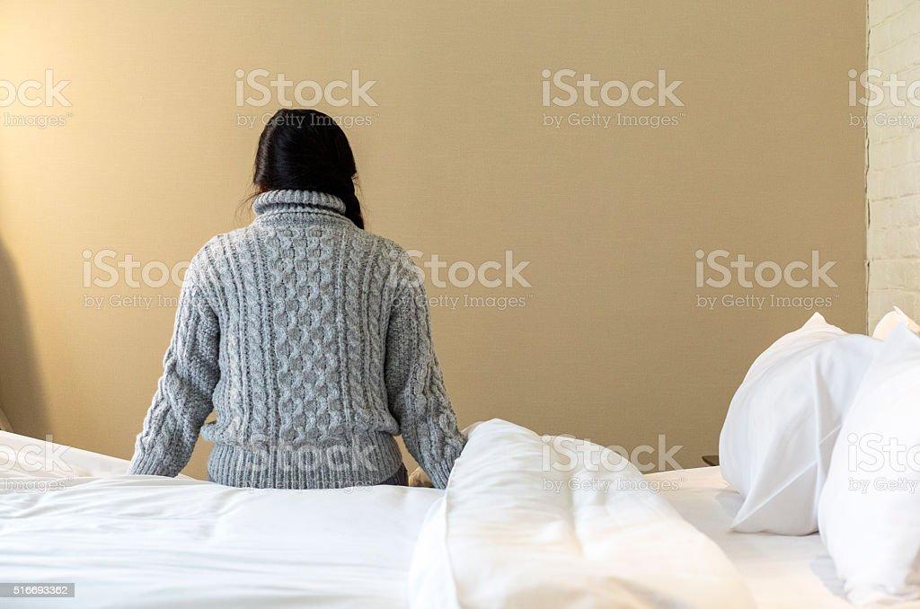 girl sitting beside bed stock photo