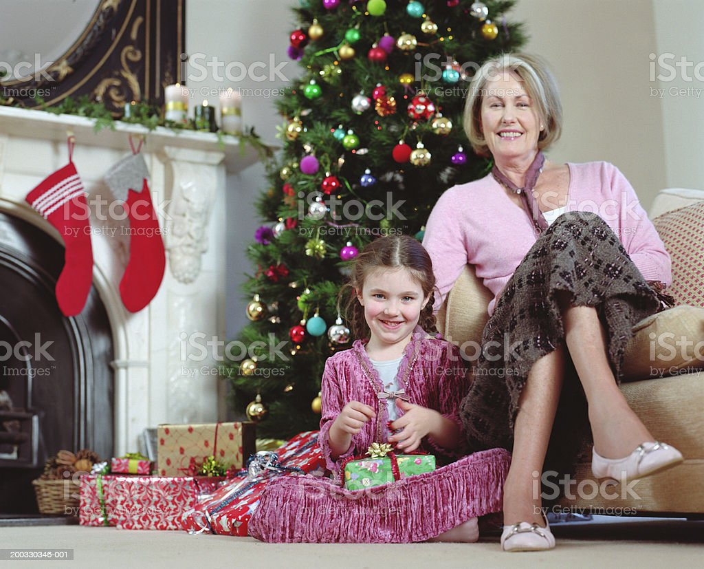 Girl (5-7) sitting by grandmother holding present, smiling, portrait royalty-free stock photo