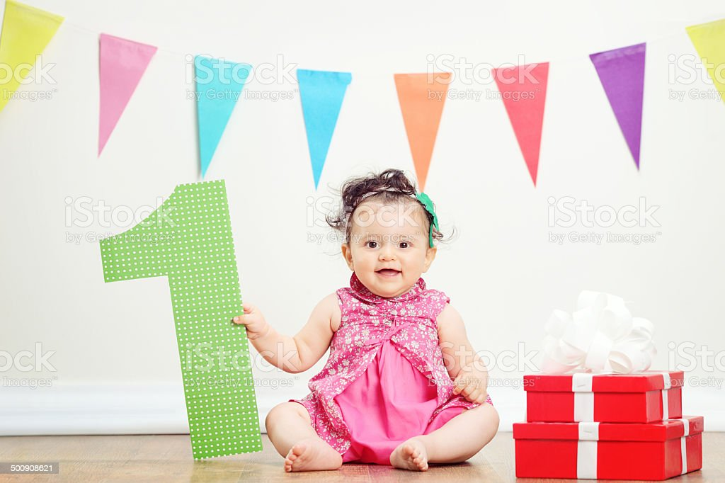 Girl sitting by pile of presents on birthday party stock photo
