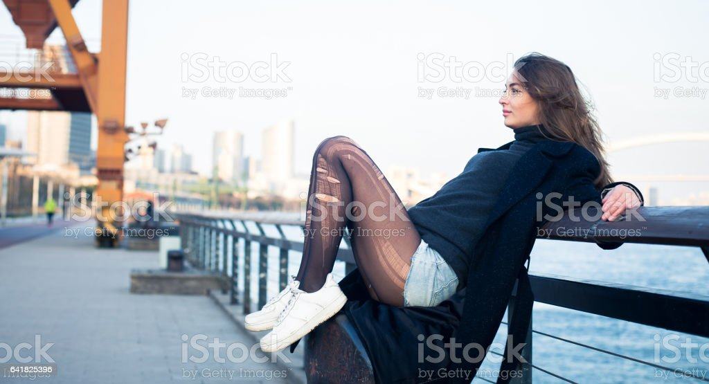 Girl sitting by the river stock photo
