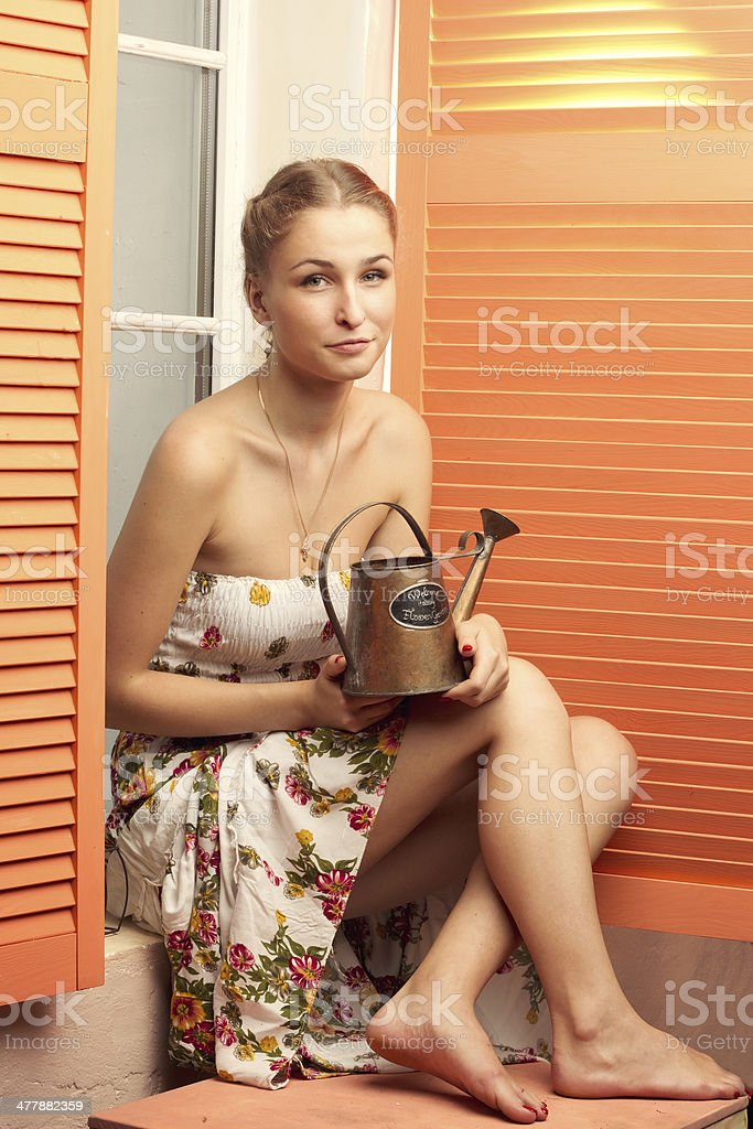 Girl sitting by window with the watering can royalty-free stock photo