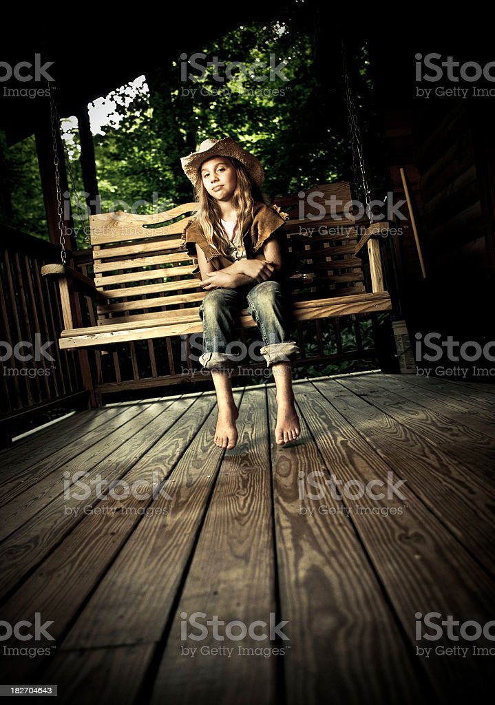 girl sitting in a big wooden swing stock photo