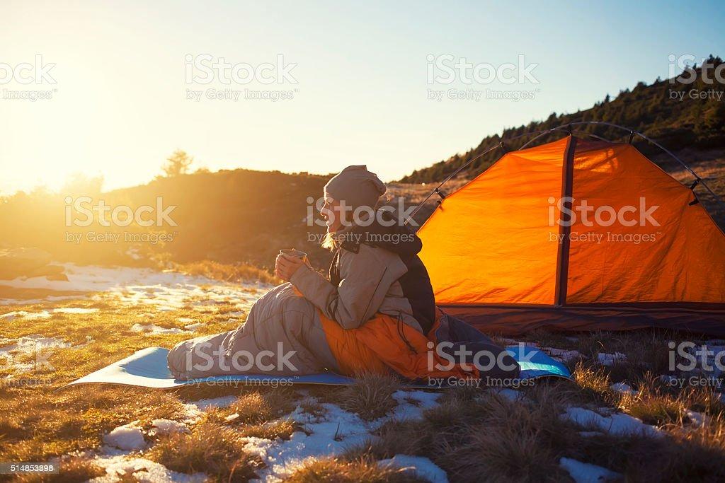 Girl sitting in a sleeping bag. stock photo